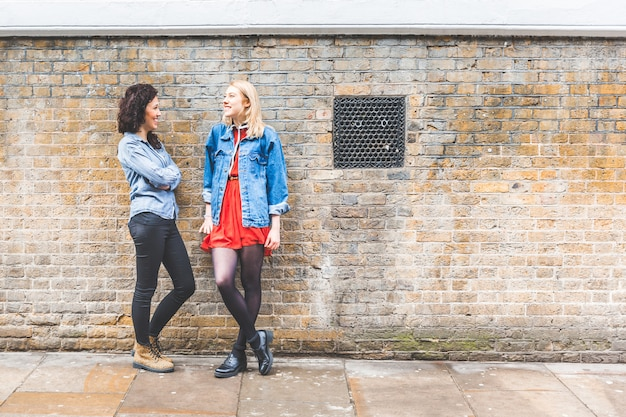 Two women leaning on a wall and talking in london