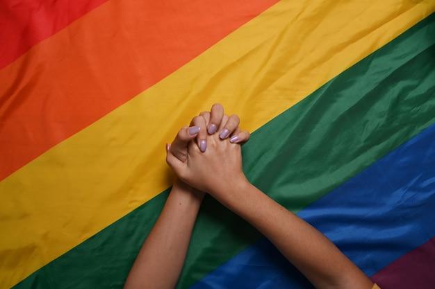 Lgbtプライドフラグを手に持っている2人の女性のレズビアンのカップル。 lgbtの概念。