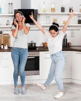 Две женщины слушают и танцуют под музыку в наушниках