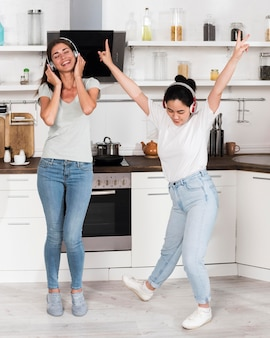 Two women listening and dancing to music on headphones