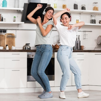 Two women listening to music on headphones and dancing