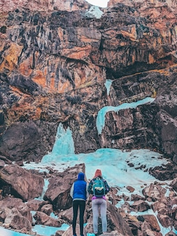 Two women look at the frozen waterfall in the mountains