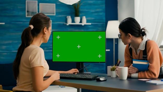 ビジネスコマースで働いているモックアップグリーンスクリーンクロマキーでコンピューターを見ている2人の女性。オフィスデスクは、隔離されたホームオフィスpcが装備されています