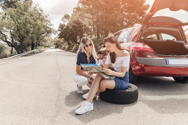 Two women looking at map sitting near the broken down car on road