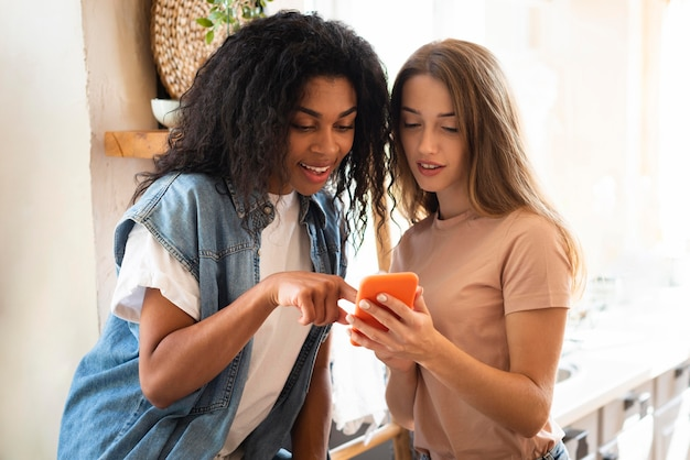 Two women looking together on smartphone at home