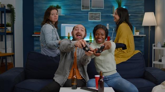 Due donne che perdono videogiochi online usando il joystick che giocano per una competizione di gioco. amici multietnici che bevono birra, socializzano, si divertono insieme seduti sul divano a tarda notte