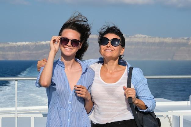 Две женщины, мать и дочь-подросток, наслаждаются морским путешествием на круизном лайнере, волосы развеваются на ветру