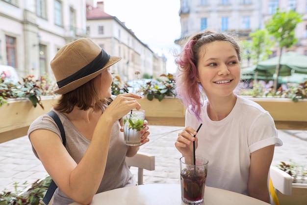 街の屋外カフェに座って話し、夏の氷の冷たい飲み物、モヒート、カクテルを飲む2人の女性の母と10代の娘