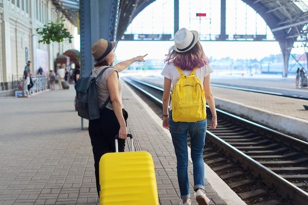 두 명의 여성 어머니와 10대 딸이 기차역에서 짐을 들고 걸어가고 있습니다. 기차의 도착을 기다리는 사람들, 뒷모습