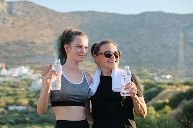 Two women mother and teenage daughter drinking water on hot summer day after exercise and jogging outdoors in mountains