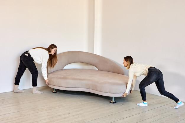 2人の女性がラウンジで新しいソファを移動します