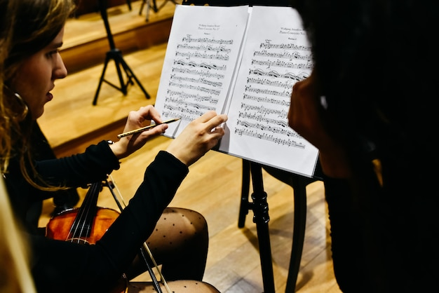 Two women musicians correcting a score with a pencil before the orchestra begins to play.