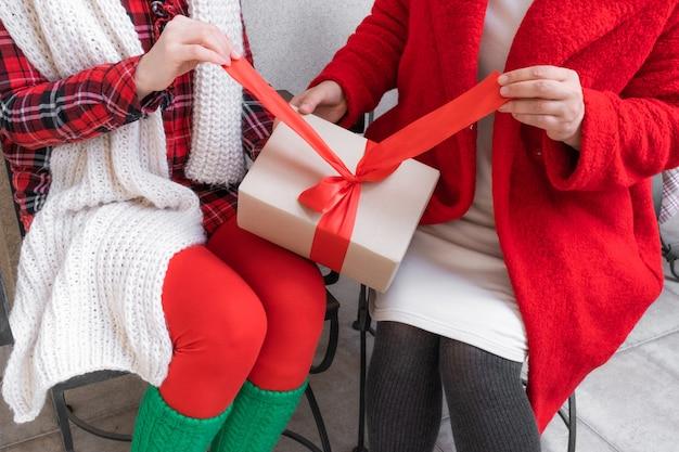 Две женщины открывают подарки накануне праздников рождества и нового года.