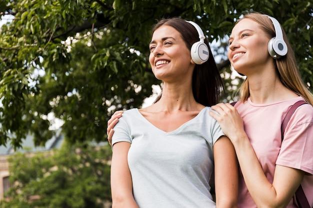 屋外でヘッドフォンで音楽を聴く2人の女性
