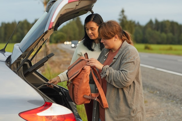 Two women packing backpacks into the car they travelling by car during their vacation