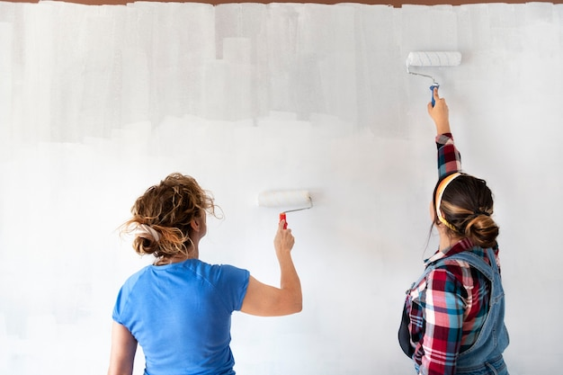 Two women painting new apartment walls in color white with paint roller renovating home copy space