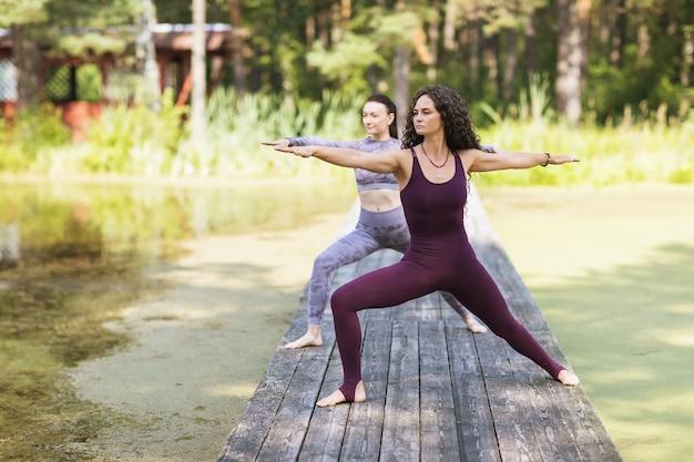 2人の女性が公園の木橋でvirabhadrasana運動戦士ポーズを実行します