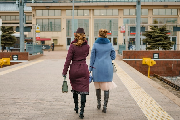 Two women on the platform of the railway station waiting for the train