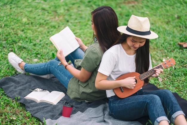 Две женщины играют на укулеле и читают книгу вместе в лесу