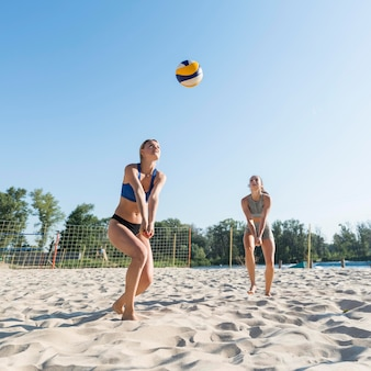 Two women playing volleyball on the beach