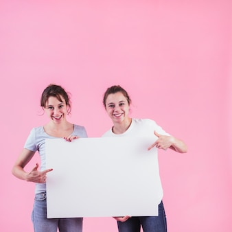 Two women pointing finger over the blank placard standing against pink backdrop