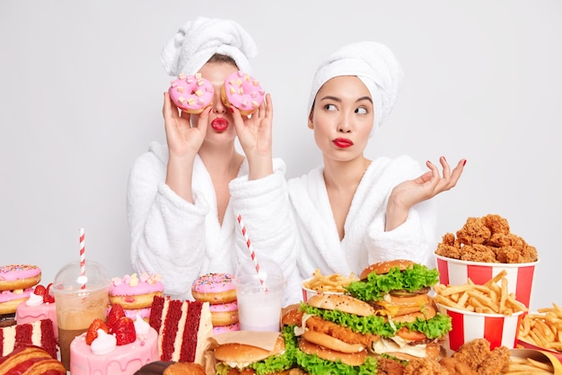 Two women pose near table full of delicious appetizing snacks prefer cheat meal istead of healthy one.