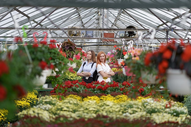 Two women posing in a greenhouse between hundreds of flowers
