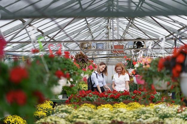 百花の間の温室でポーズをとる2人の女性