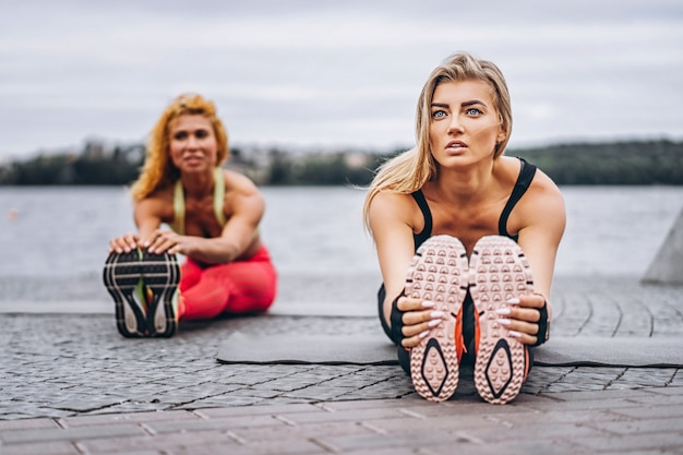 2人の女性が、水の近くの通りのマットでヨガの練習をします。アクティブなライフスタイル。ヨガのコンセプト