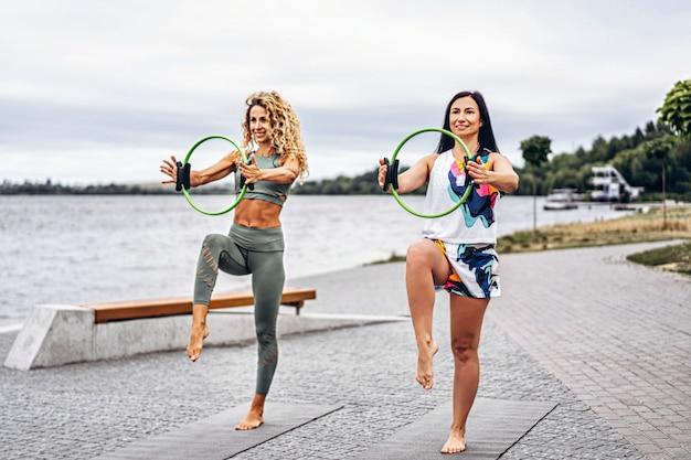 2人の女性が、水辺の路上で、特別なスポーツサークルのあるマットでヨガの練習をします。アクティブなライフスタイル。ヨガのコンセプト