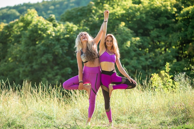 晴れた日に2人の女性が自然の中でヨガを練習します