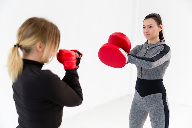 Two women practicing box at gym