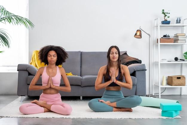 居心地の良い家で瞑想にポーズをとるヨガ蓮の練習をしている2人の女性