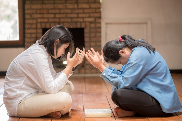 두 여성이 함께 기도하고 서로를 격려합니다.