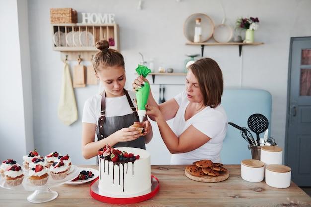 Две женщины вместе готовят вкусные сладости на кухне.