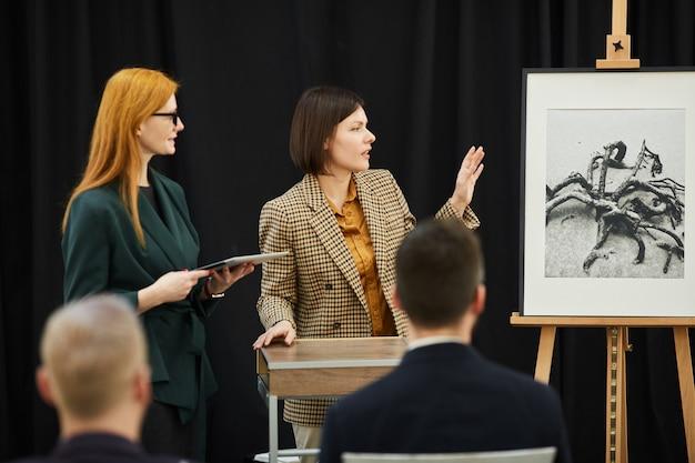 絵画を提示する2人の女性