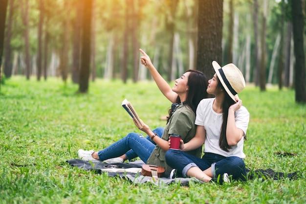 Две женщины вместе читают книгу, сидя и глядя в лес