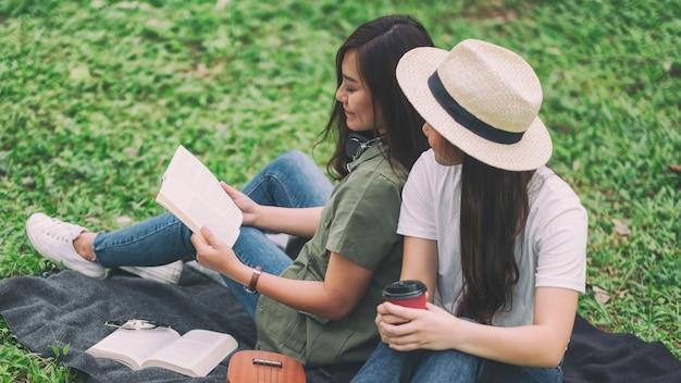 Две женщины вместе читают книгу, сидя в лесу
