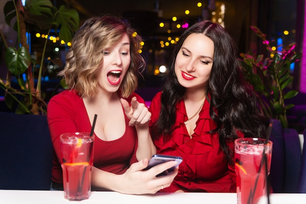 Two women in red dresses drink cocktails and celebrate in a nightclub or bar