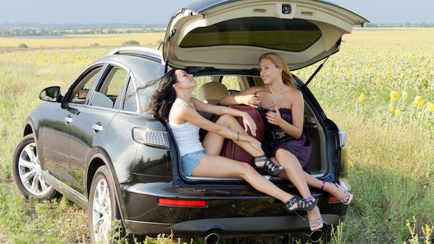 ステーションワゴンの上げられたトランクの陰でリラックスしながら田舎を長い旅で休憩する2人の女性