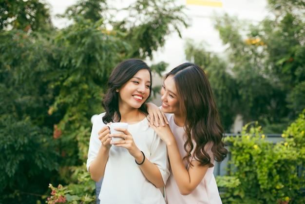 Two women relaxing on rooftop garden drinking coffee