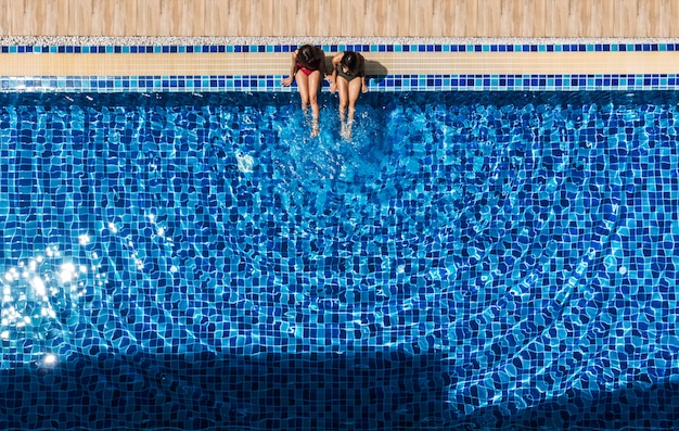 Two women relaxing and sitting at swiming pool.