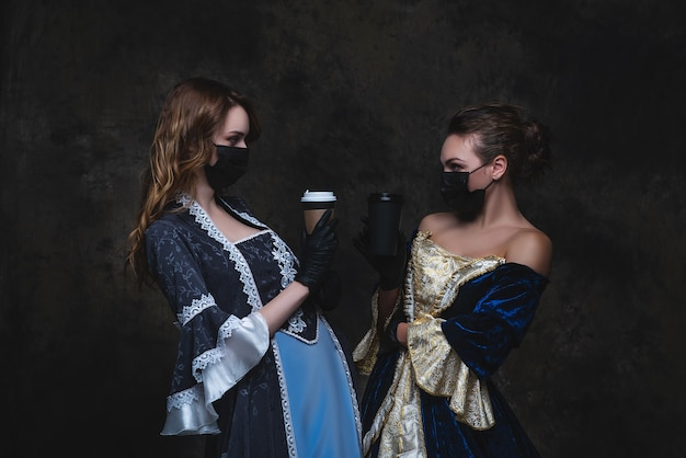 Two women in renaissance dress drinking coffee, old and new concept