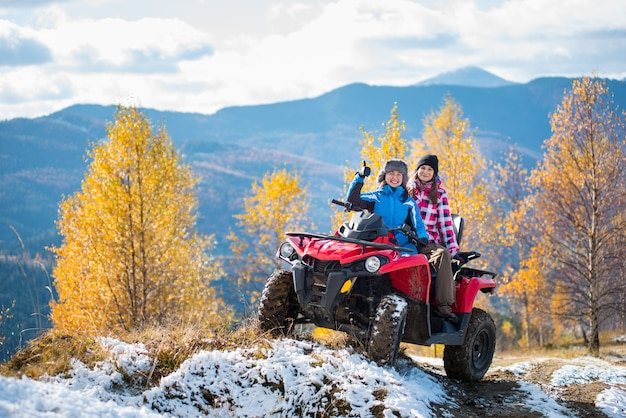 Two women riders atv on a snow-covered trail at sunny autumn day