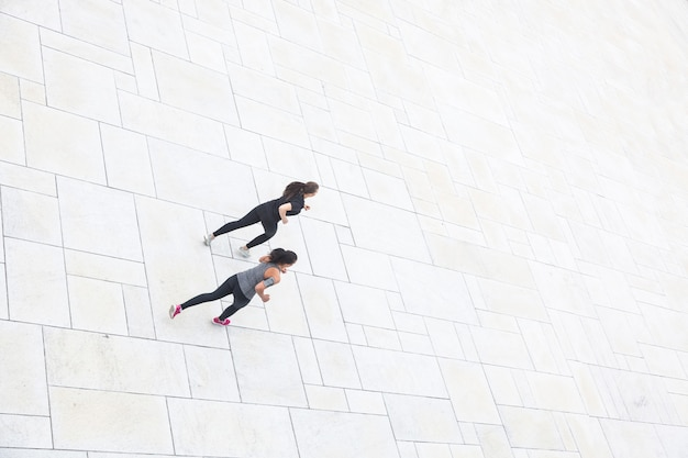 Two women running in the city, aerial view