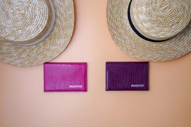 Две женские пляжные соломенные шляпы канотье, паспорта на бежевом фоне. концепция поездки, путешествий и туризма.