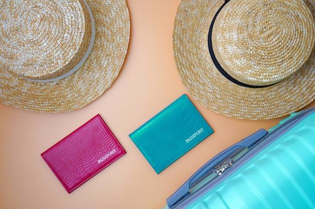 Две женские пляжные соломенные шляпы, паспорта и чемодан на бежевом фоне.