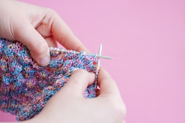 Two women's hands knitting needles from pink and blue yarn on a pink background.