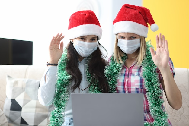 Two women in santa claus hats waving to laptop.