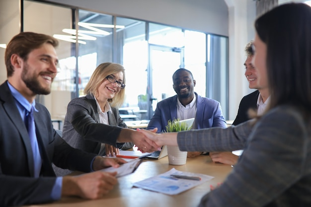 Two women shaking hands and looking at each other with smile while their coworkers sitting at the business meeting.